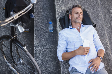 Man with closed eyes lying on stairs with cell phone and earbuds next to bicycle - DIGF02589