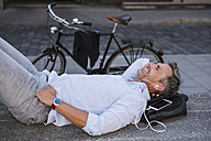 Smiling man with closed eyes lying on stairs with cell phone and earbuds next to bicycle - DIGF02592