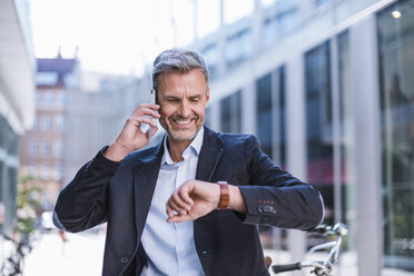 Smiling businessman on cell phone in the city checking the time - DIGF02595