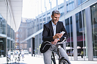Smiling businessman with bicycle and cell phone in the city - DIGF02598
