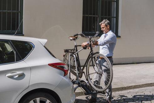 Man fixing bicycle on trailer at car - DIGF02601