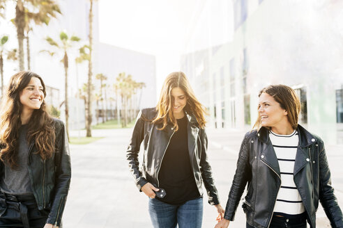 Three happy friends wearing black leather jackets - GIOF02948