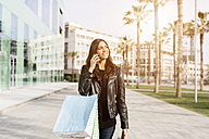 Portrait of smiling woman with shopping bags on the phone - GIOF02957