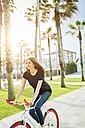 Smiling young woman on fixie bike - GIOF02960