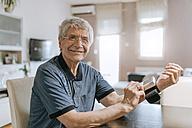 Smiling senior man taking his blood pressure - ZEDF00747