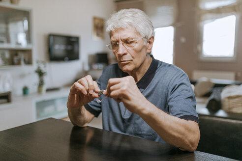 Senior man examining hearing aid - ZEDF00750