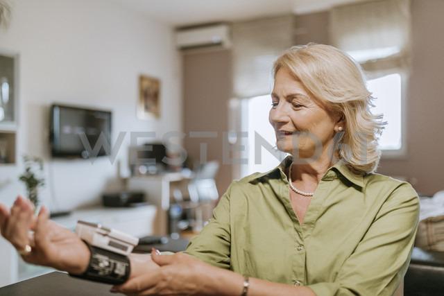 Smiling senior woman taking her blood pressure - ZEDF00753