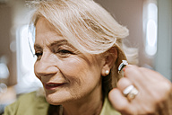 Senior woman applying hearing aid - ZEDF00759