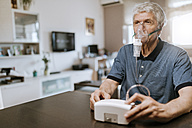 Senior man using inhaler at home - ZEDF00765