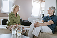Senior couple at home talking on couch - ZEDF00768