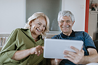 Happy senior couple at home sitting on couch sharing tablet - ZEDF00777