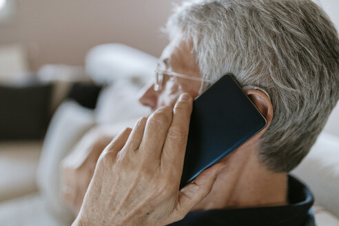 Senior man with hearing aid on cell phone - ZEDF00780