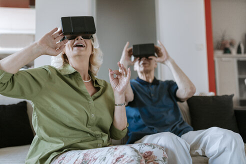 Happy senior couple at home sitting on couch wearing VR glasses - ZEDF00783