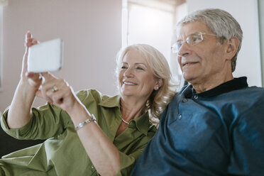 Senior couple at home sitting on couch taking a selfie - ZEDF00786