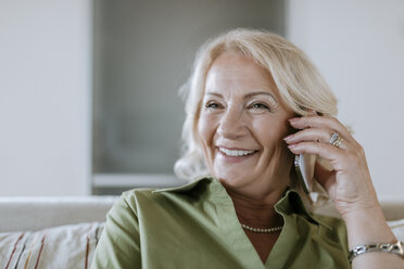 Smiling senior woman at home on cell phone - ZEDF00795