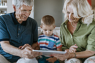 Grandparents and grandson at home sitting on couch sharing tablet - ZEDF00798