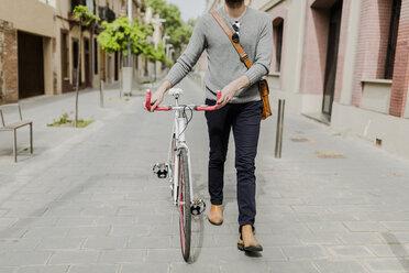 Young man pushing his bike, partial view - GIOF02962
