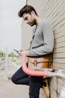 Young man leaning against wall using cell phone - GIOF02968