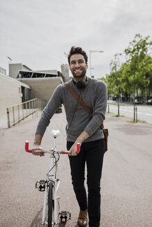 portrait of smiling young man with headphones pushing his bike - GIOF02974