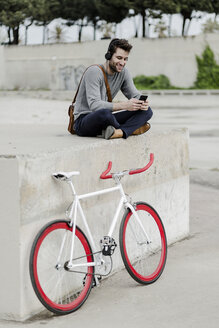 Young man with racing cycle sitting on a wall listening music with headphones - GIOF02977