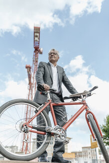 Portrait of senior businessman with bicycle in front of construction crane - GUSF00047