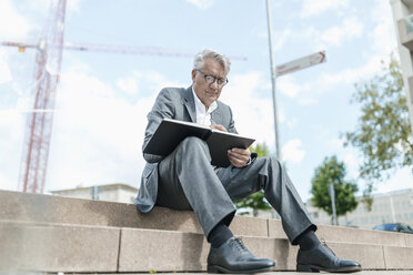 Portrait of senior businessman sitting on stairs with notebook in front of construction crane - GUSF00050