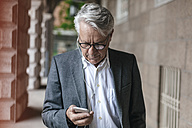Senior businessman with earphones looking at cell phone - GUSF00053