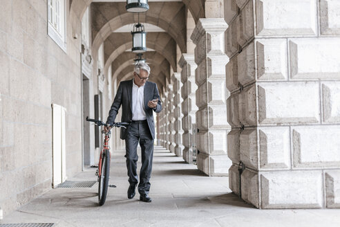 Senior businessman looking at cell phone while pushing his bicycle - GUSF00056