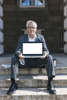 Portrait of senior businessman sitting on stairs showing  laptop - GUSF00059