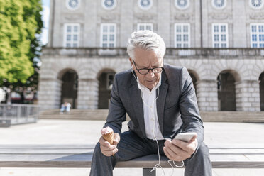 Senior businessman with ice cream cone sitting on bench looking at smartphone - GUSF00062