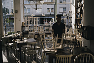 Man clearing cafe at closing time - KNSF01885