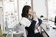 Businesswoman in cafe kissing her baby - KNSF01894