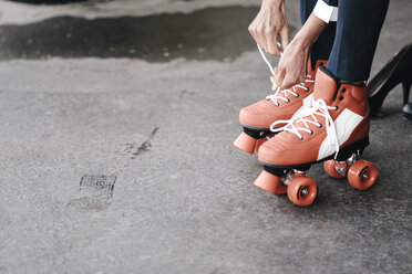 Businesswoman tying her roller skates, close up - KNSF01897