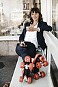 Businesswoman wearing roller skates, drinking coffee and using smartphone - KNSF01900