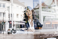 Businesswoman sitting in cafe, daydreaming - KNSF01903