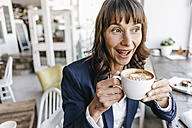 Businesswoman sitting in cafe, drinking coffee - KNSF01909