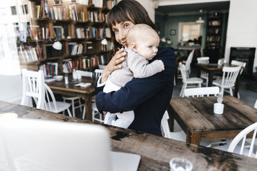 Businesswoman in cafe holding baby - KNSF01912