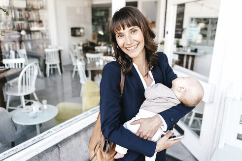 Businesswoman in cafe holding sleeping baby - KNSF01915