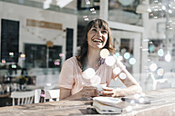 Woman sitting cafe, watching soap bubbles - KNSF01933