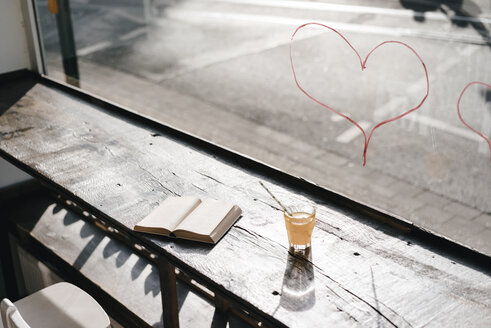 Book and drink on table in front of a window with lipstick hearts - KNSF01945