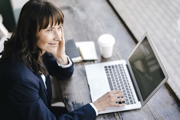 Businesswoman sitting in cafe using laptop, smiling - KNSF01954