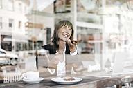 Businesswoman sitting in cafe, using smartphone - KNSF01972