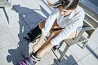 Young woman putting on inline skates - KIJF01634