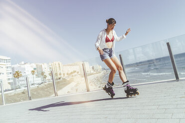 Young woman inline skating on boardwalk at the coast - KIJF01637