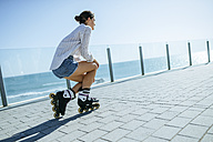 Young woman with inline skates on boardwalk at the coast - KIJF01640