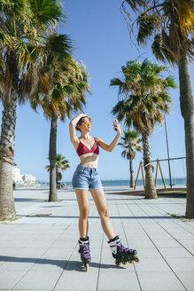 Young woman on inline skates taking a selfie on boardwalk - KIJF01646