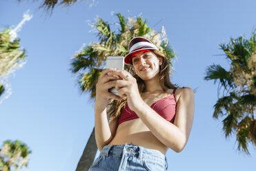 Young woman with sun visor and bikini using cell phone - KIJF01655