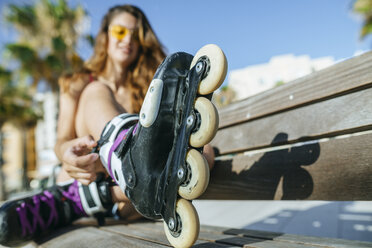 Close-up of woman with inline skates sitting on a bench - KIJF01658