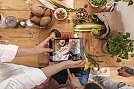 Friends cooking together taking picture of prepared vegetables with tablet, top view - GUSF00064