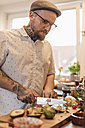 Tattooed man preparing food in the kitchen - GUSF00085